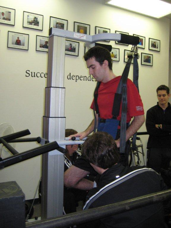 Simulating a walking motion while being suspended in a harness over a treadmill